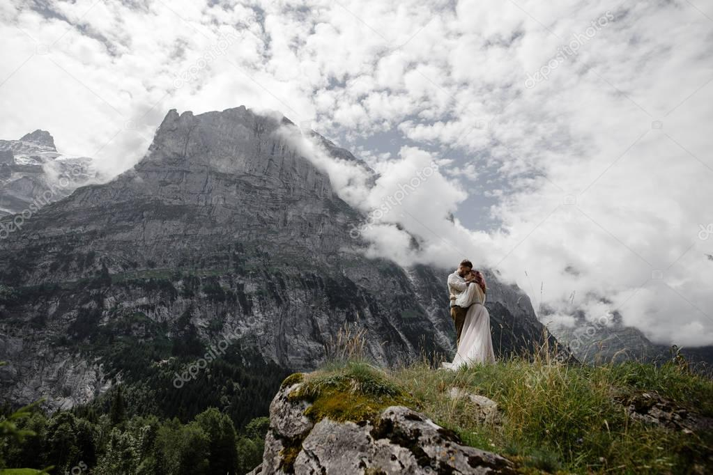 beautiful young wedding couple hugging in majestic mountains, Alps