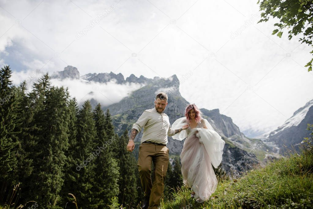 beautiful young bride and groom holding hands and walking on green mountain meadow in  Alps