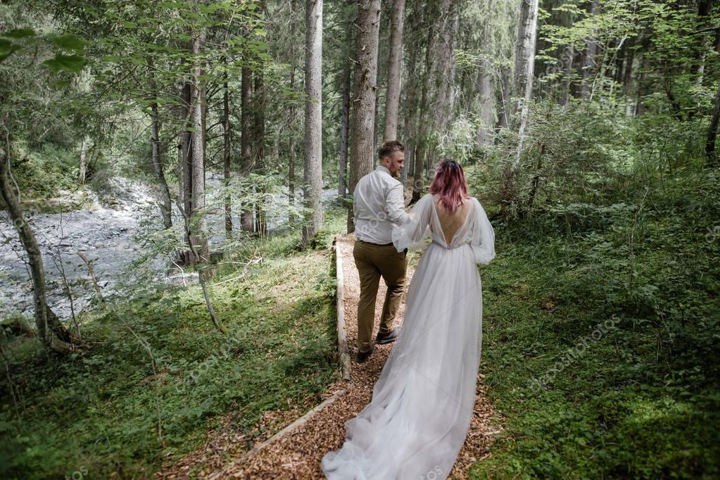 back view of beautiful young wedding couple walking on mountain path in Alps