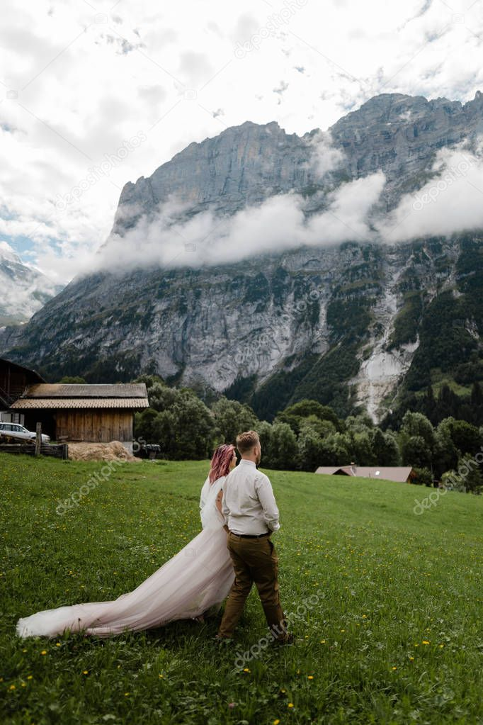 young bride and groom walking on green mountain meadow with clouds in Alps