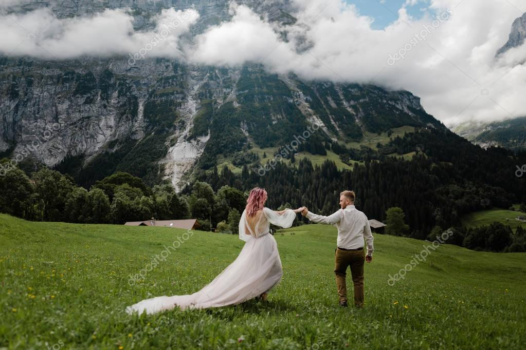 young bride and groom holding hands on green mountain meadow with clouds in Alps