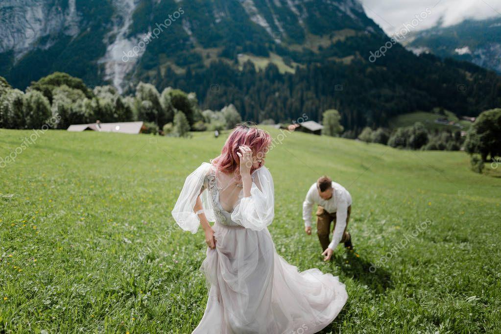 happy bride in wedding dress and groom walking on green mountain meadow in Alps