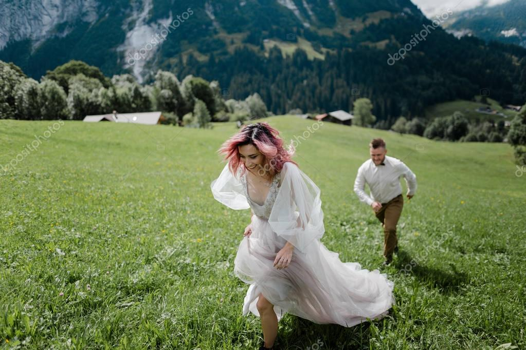 young bride with pink hair and groom walking on green mountain meadow in Alps