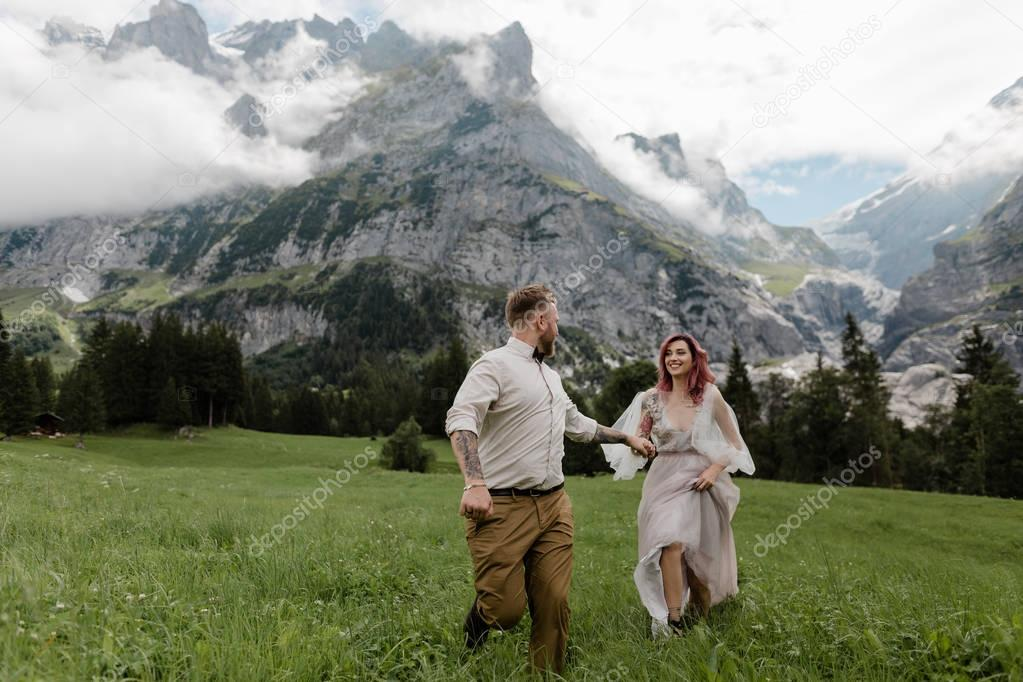 happy bride in wedding dress and groom holding hands and walking on alpine meadow with clouds