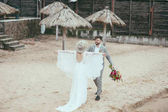 Fotografie beautiful happy bridal couple in bohemian style on beach