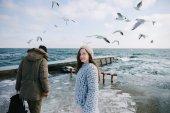 belle giovani coppie che camminano in riva al mare in inverno
