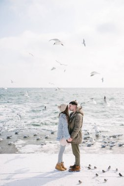 young couple holding hands and kissing on seashore in winter