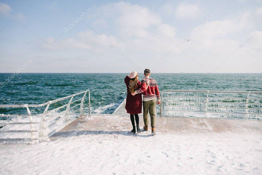 back view of stylish couple hugging on quay near sea