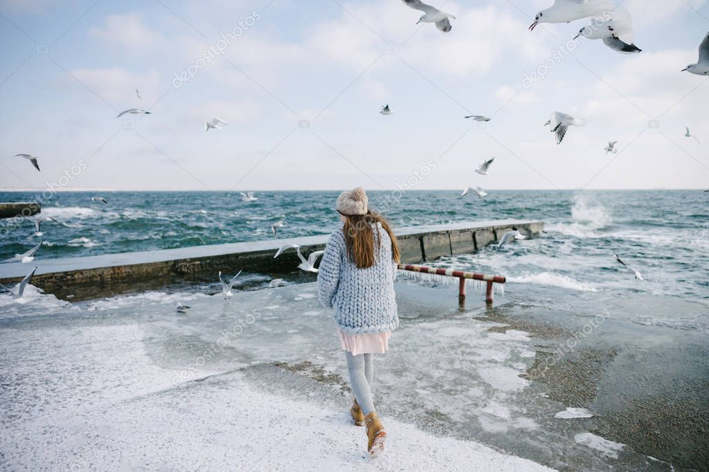 back view of young woman walking on winter seashore with seagulls