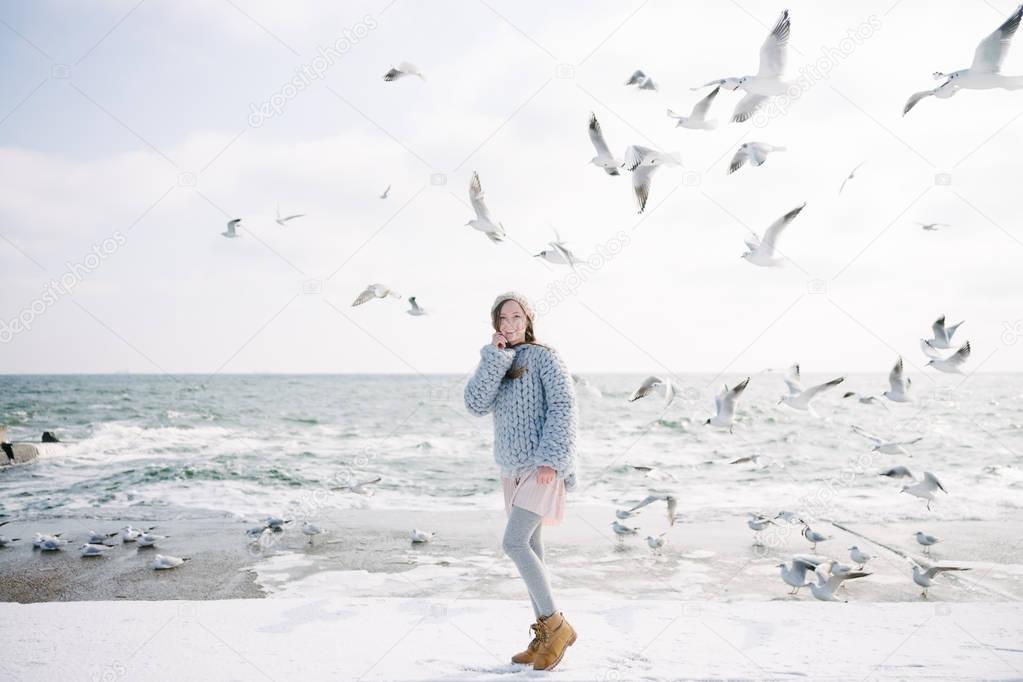 young woman in merino wool sweater on winter seashore with seagulls