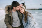 young smiling couple embracing on winter sea shore