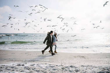 Young couple running on winter sea shore with seagulls stock vector