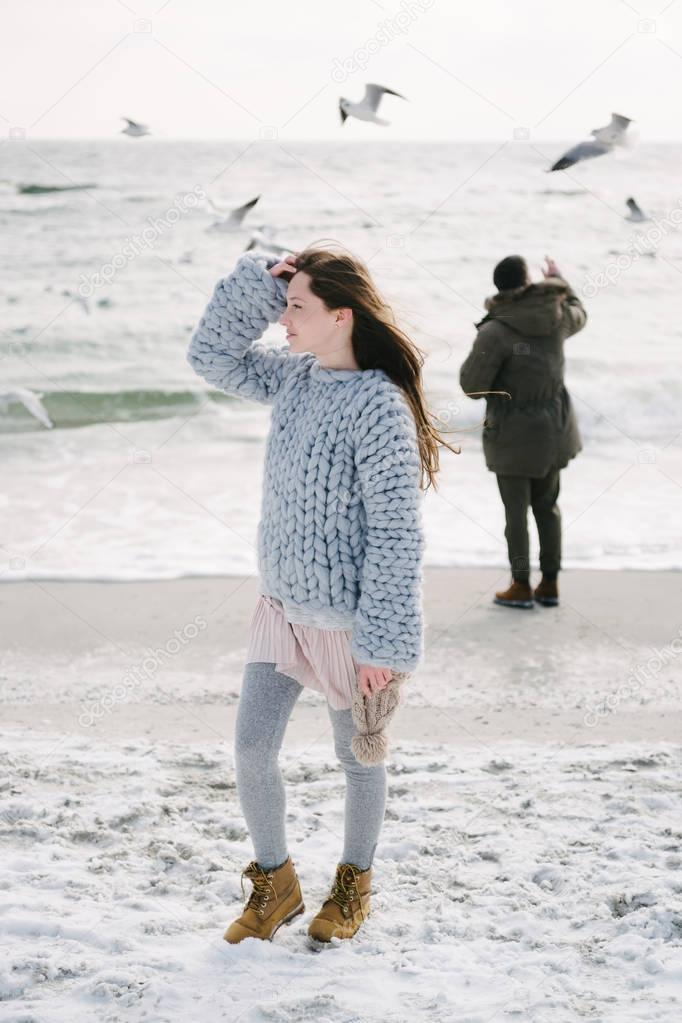 stylish girl in merino sweater on winter seashore, boyfriend standing behind