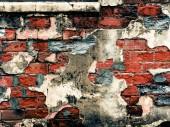 Zoufalý cihlová zeď s trhlinami a rozbité omítky