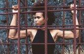 Fotografia Tutto il potere al popolo. Omaggio a Black Panther Party e Angela Davis, è stato ispirato dalla sua immagine famosa stencil - Free Angela e tutti i prigionieri politici dagli anni  60. Bella ragazza atleta di misura con afro dietro le sbarre di ferro arrugginito