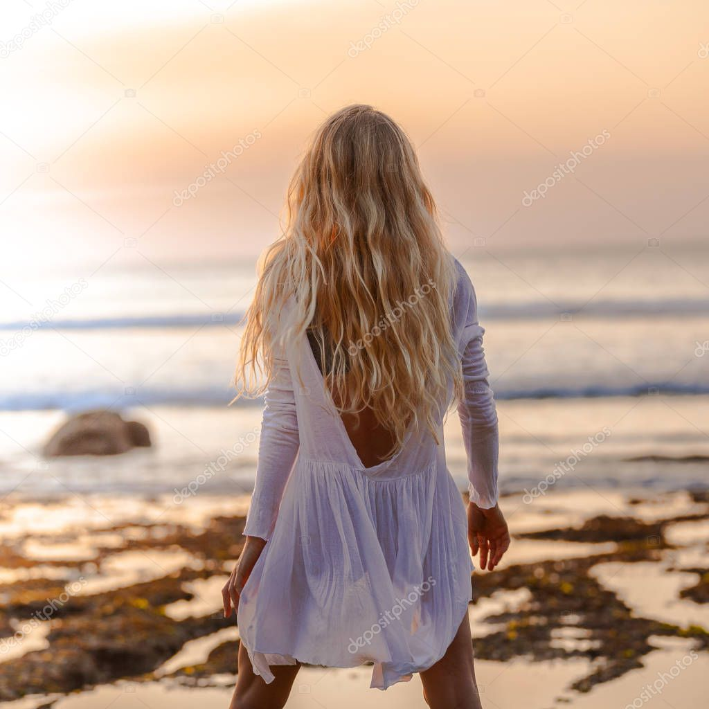 Beautiful blonde girl with long hair in short white dress looking at sunset on the beach in Bali, Indonesia, from behind standing
