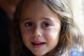 Egy 4 éves lány egyenesen a kamerába néz.