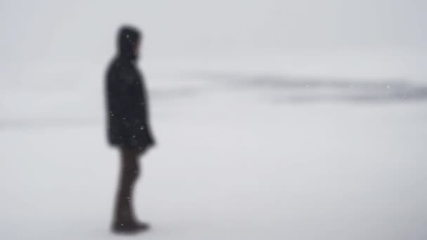 In the snowstorm, the male figure walks leisurely not in focus.