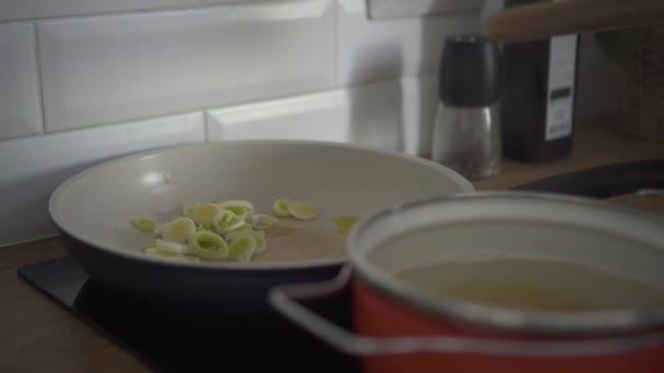Šéfkuchař smaží zeleninovou cibuli na pánvi. na oleji v kuchyni. žena v domácnosti vaří čerstvé jídlo. Spbd