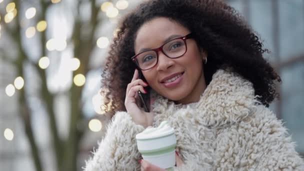 Frau im Freien hört Gespräche auf dem Smartphone. weiblich mit wiederverwendbarer Kaffeetasse in der Hand. spbi