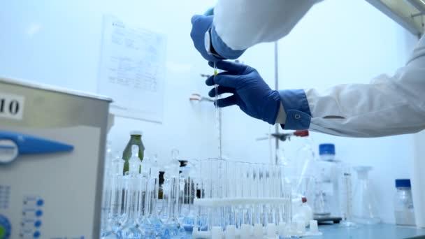 gyógyszerész kezek pipettával és injekciós üveggel. mintát dobnak a kémcsőbe. Laboratóriumi berendezések gyógyfürdői