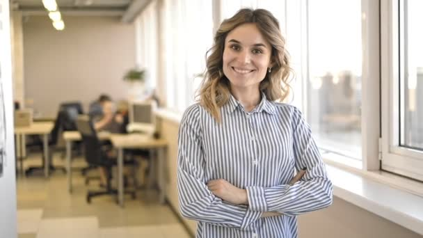 business woman with crossed arms standing in office smiling and posing at camera Irrl