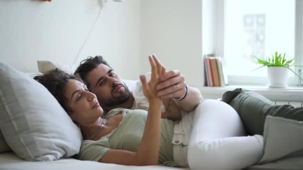pěkný pár v posteli mluvící a dotýkající se rukou uvolnil Spbd. přítelkyně a přítel v hipsteru