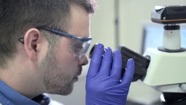 Männliche Fachkraft nutzt Mikroskop während des Arbeitstages in pharmazeutischen Labor spbas.