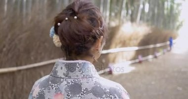Following Beautiful young woman in Kyoto bamboo forest.