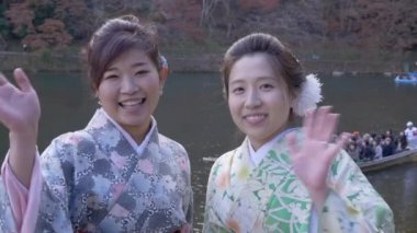 Japanese women in kimono wave as tourist boat goes past