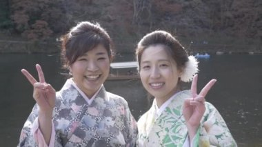Pretty young Japanese women give peace sign by the river.