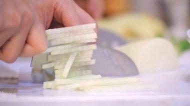 Slicing white radish with a sharp knife