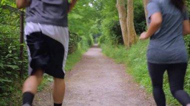 Friends run down a beautiful path in slow motion