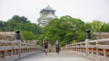 Friends running across a beautiful bridge in slow motion