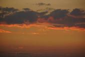 Nádherné barevné mraky na večerní obloze. Jasné růžové mraky na obloze při západu slunce. Krásná večerní obloha. Abstraktní, purpurově růžové pozadí. Pulzující barevná fotografie.