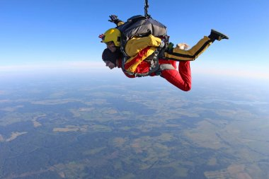 Skydiving. Tandem passenger and instructor are flying together in the sky.