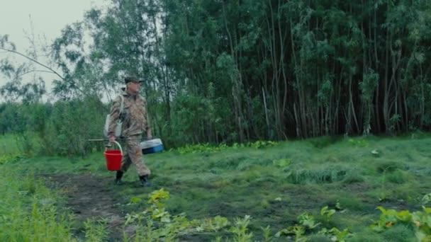 Rybář, pěší podél cesty rybář šel na břehu řeky a sundal si klobouk a rozhlédl se kolem