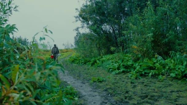 Rybář jde do řeky, muž lovným zařízením jde podél cesty hustým křovím na břehu řeky