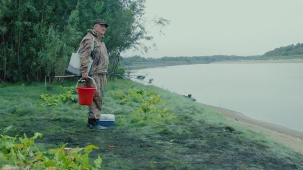 Rybář na břehu růst portrét rybáře s vybavením na břehu řeky