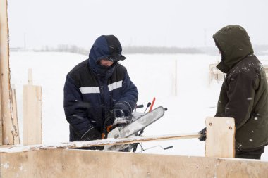 Two workers in overalls at a construction site