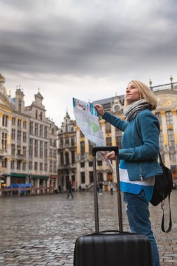 Woman tourist goes with a suitcase at the Grand Place in Brussels, Belgium