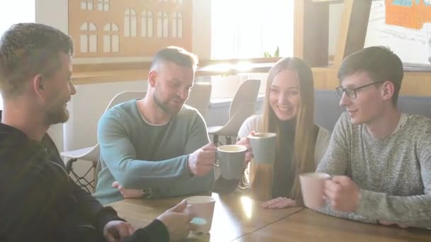 Happy group of friends or business colleagues drinking coffe and laughing and using computer together in a small cafe or wine bar