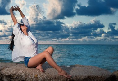 Beautiful young brunette woman stretching on a rock by the ocean