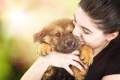 Fotografie Krásná mladá brunetka žena s blažený výraz drží mladé štěně venku s slunečního záření