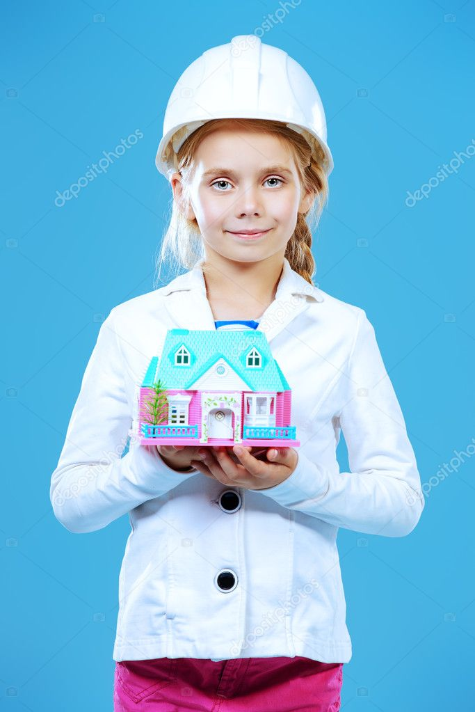 family home. Little girl in a builder helmet  holding house in her hands.