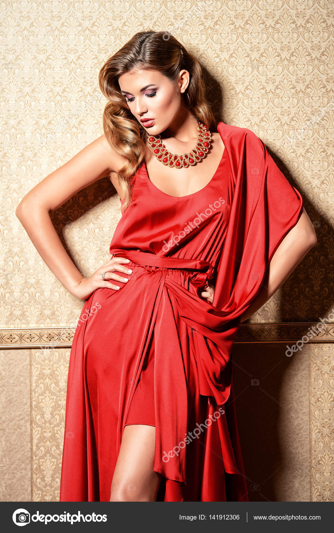 d2be69ed0b9d Bella donna affascinante che porta sera vestito rosso e una collana di  gemme che posano sopra lussuoso sfondo vintage. Bellezza
