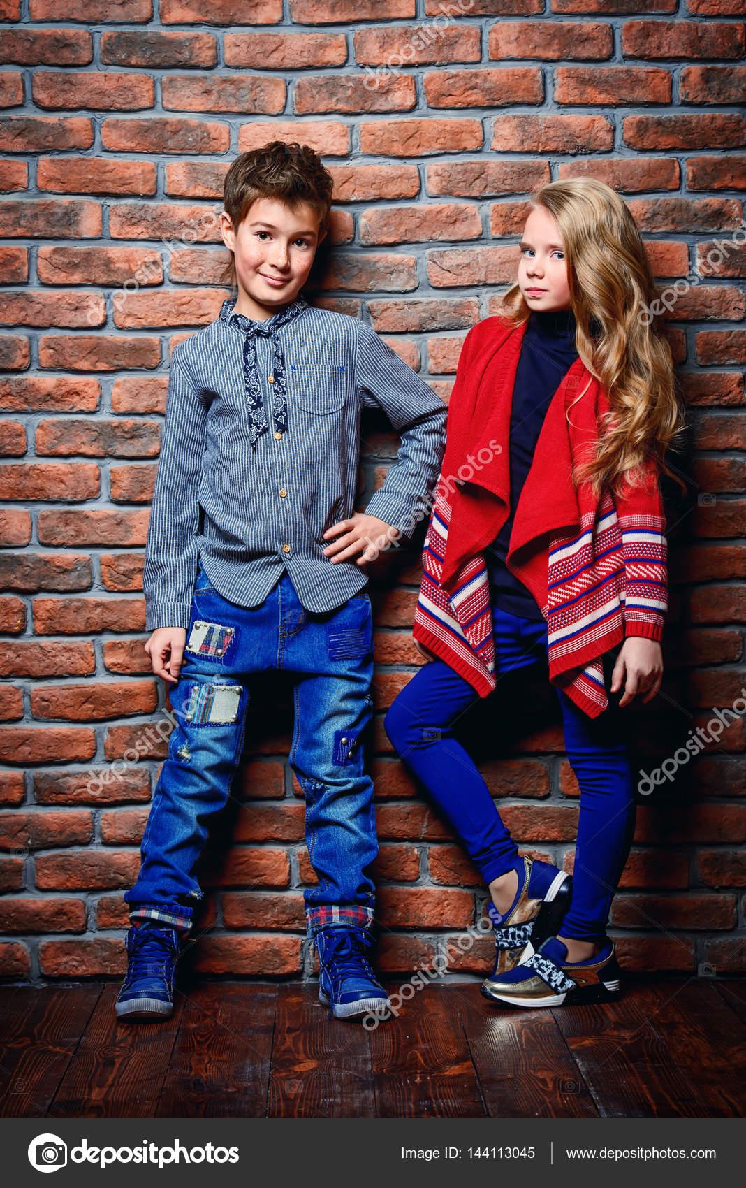25c79a49b Moda infantil. Moderno niño de nueve años y una niña posando en el estudio  sobre fondo de pared de ladrillo. Ropa para niños - imágenes: niños con ropa  de ...
