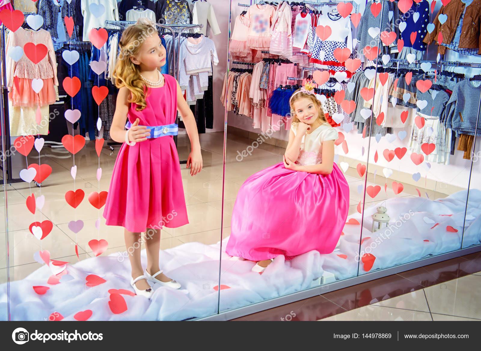 34cbf46f28b1be Дві маленькі милі дівчата в красиві сукні позують у вікні магазин дитячого  одягу. Малюка моди. Сезонні продажу та покупки — Фото від ...