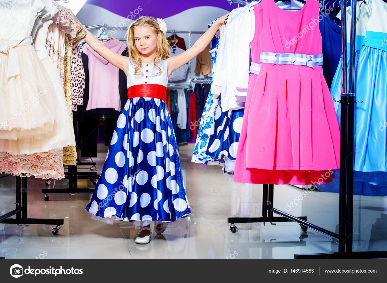 Гарненька дівчинка дитини вибір нове плаття в магазин дитячого одягу.  Сезонні продажу та покупки. Малюка моди — Фото від prometeus 00c93be940542
