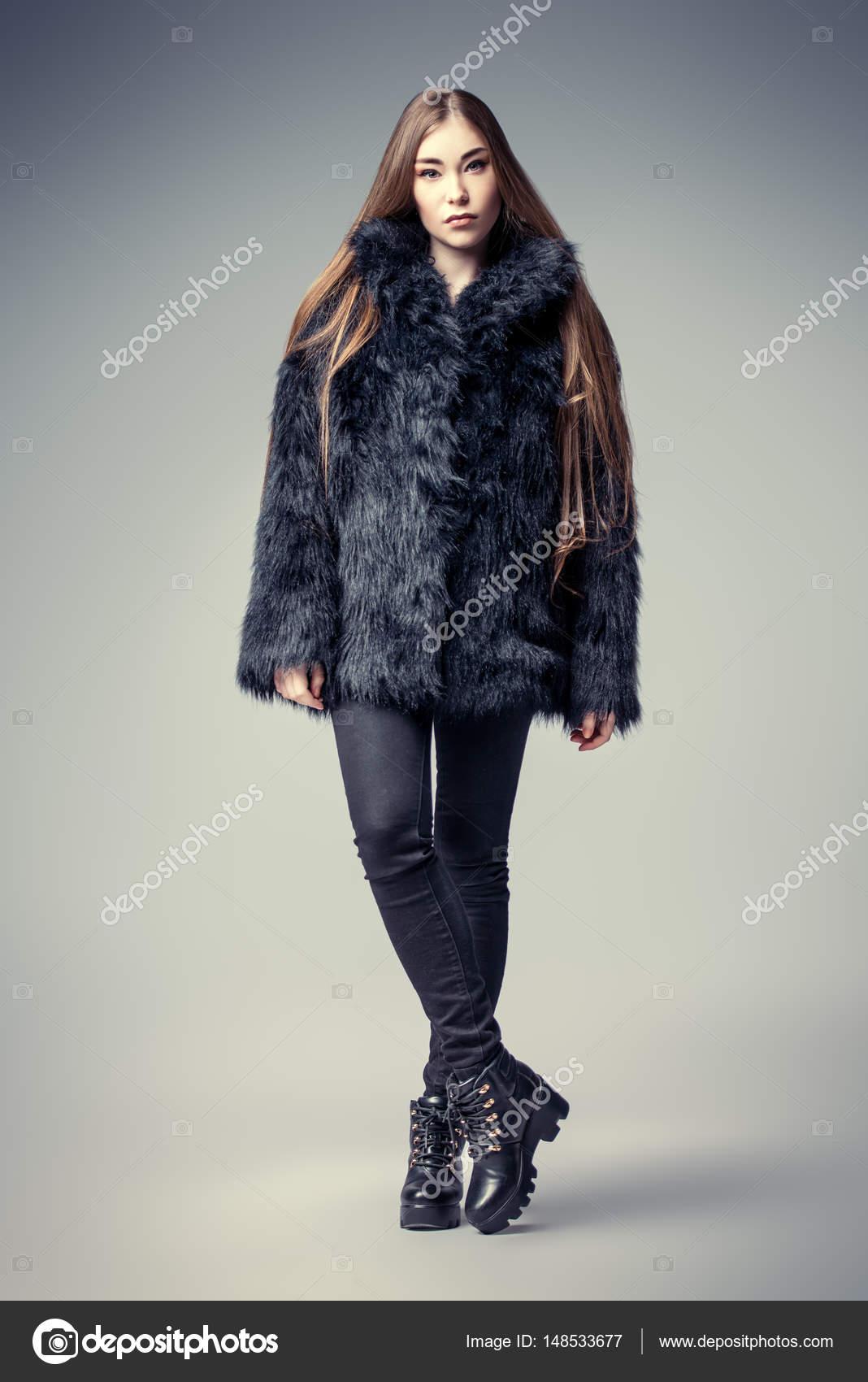 4eaad2ac2b0 Po celé délce portrét módní model s krásnými dlouhými vlasy pózuje ve  studiu v černý kožich — Fotografie od ...